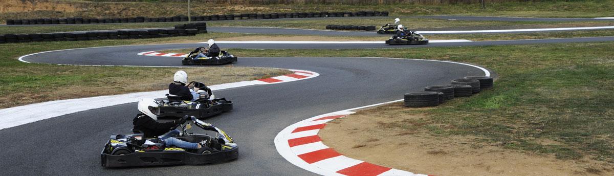 pilotes de karts dans un virage piste de karting plein air